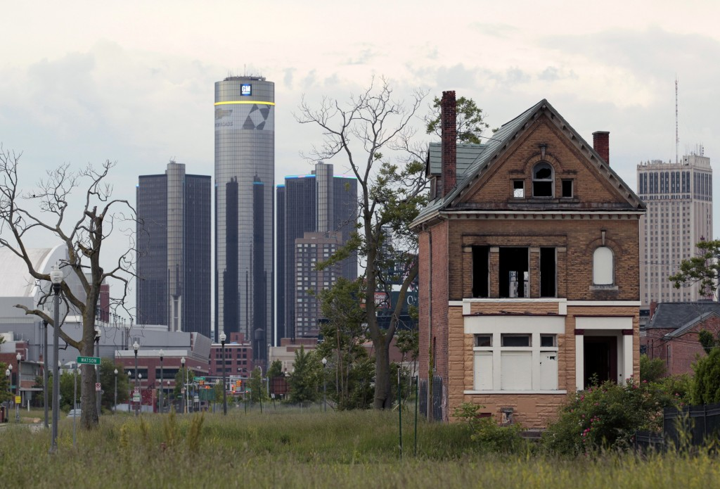 The Renaissance Center, left, the global headquarters of General Motors Co. (GM) stands in Detroit, Michigan, U.S., on Thursday, June 6, 2013. Detroit became the biggest U.S. city to file for bankruptcy on July 18, 2013, seeking court protection from creditors while it tries to eliminate a budget deficit and cut long-term debt. Photographer: Jeff Kowalsky/Bloomberg via Getty Images