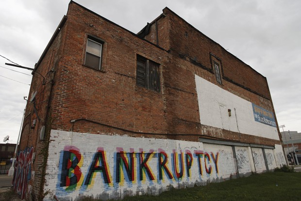 """The word """"Bankruptcy"""" is painted on the side of a building in Detroit, Michigan in this October 25, 2013 file photo. Detroit is eligible for banktrupcy, a U.S. judge ruled on December 3, 2013 after determining the city is broke and had too many creditors to make negotiations over more than $18 billion in city debts and other obligations possible. The ruling by Judge Steven Rhodes makes Detroit's case officially the biggest municipal bankruptcy in U.S. history. REUTERS/Joshua Lott/Files (UNITED STATES - Tags: LAW REAL ESTATE BUSINESS POLITICS) - RTX162AL"""