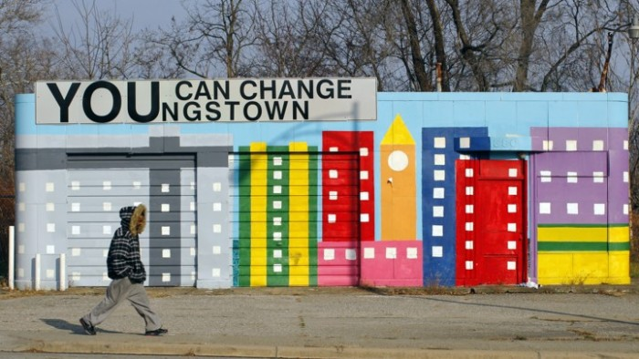 A man walks past a painted building in Youngstown, Ohio November 21, 2009. Youngstown has 4,500 vacant structures in a city of about 75,000 people, and about 22,000 vacant parcels of land. REUTERS/Brian Snyder (UNITED STATES CITYSCAPE SOCIETY) - RTXR04Y